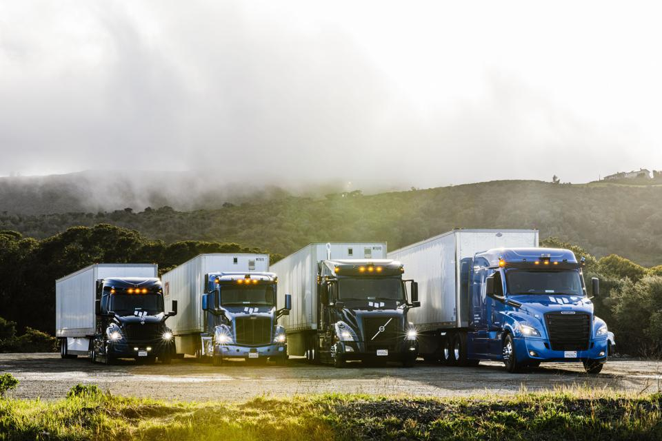 Four tractor-trailers parked.